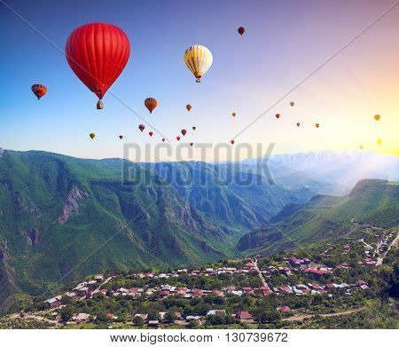 Beautiful landscape with green mountains and air balloons