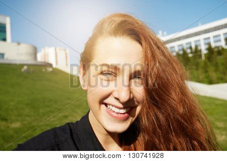 Close Up Of Pretty Girl Looking And Smiling At The Camera Against Green Urban Background In The Publ