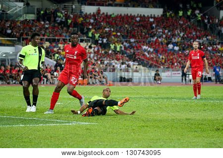 July 24, 2015- Shah Alam, Malaysia: Liverpool's Dovock Origi (red) watches a clearance by a Malaysian defender in a friendly match against Malaysia. Liverpool FC from England is on an Asia tour.