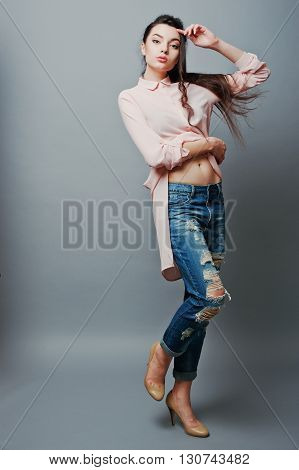 Full-length Portrait Young Sexy Brunette Girl Showing Her Navel, Wearing In Pink Blouse, Ripped Jean