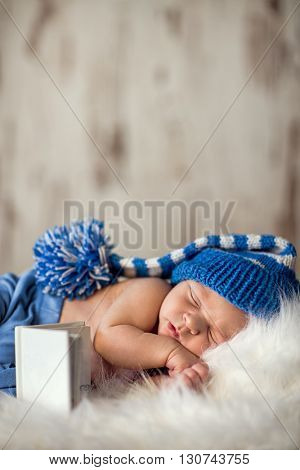 newborn baby sleeps on a white blanket, he is only 13 days old, baby wearing a white knitted cap