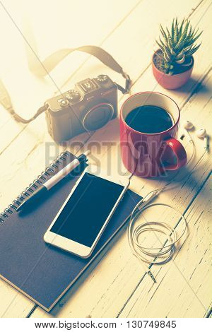 Cup of coffee smart phone notebook pen cameraearphone and cactus on wooden desk Cup of coffee with essential stuff on wooden table
