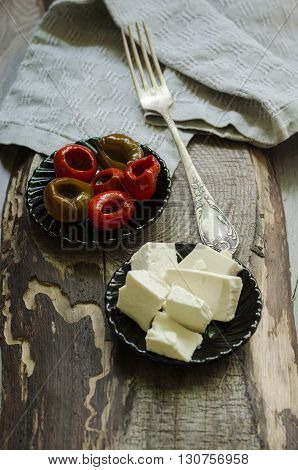 Marinated piquante cherry peppers stuffed with feta curd white cheese on wooden background