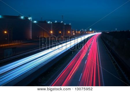 Heavy traffic on a highway. Due to the long exposure time the front and rear lamps of the cars are forming a white and a red snake of light. There are huge storage tanks on the left side.