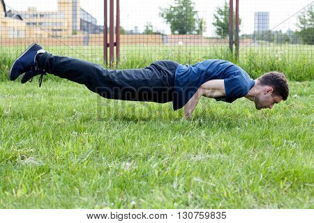 Outdoor yoga workout. Young man doing an exercise in the city park peacock pose
