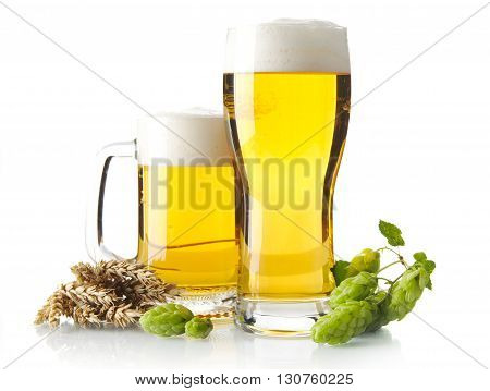 Mugs Of Beer On Table With Hop Cones, Ears Of Wheat Isolated On White