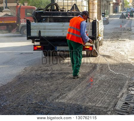 worker pours water on the milled asphalt for city street repair work