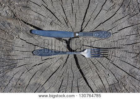 old knife and fork on grey beam cut close up