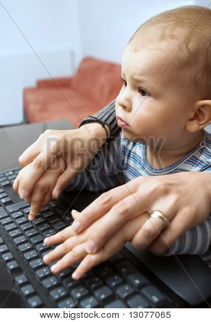One year old baby plays with a computer keyboard.