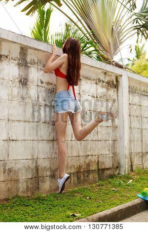 Girl In Bikini And Shorts Near Fence.