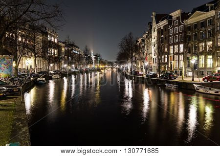 AMSTERDAM NETHERLANDS - 17TH FEBRUARY 2016: Buildings and bikes at the Keizersgracht canal intersection in Amsterdam at night.