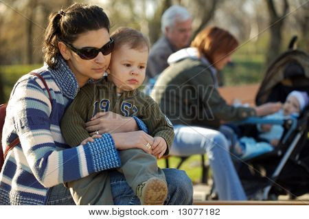 Outdoor shot of a mother and her young son relaxing while other parents are feeding their baby in the background (out of the focus).
