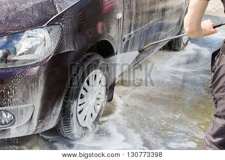 Man washing his car Wheels of a car wash using a high pressure water jet