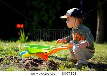 2 years old boy plays with toy tools in the garden.