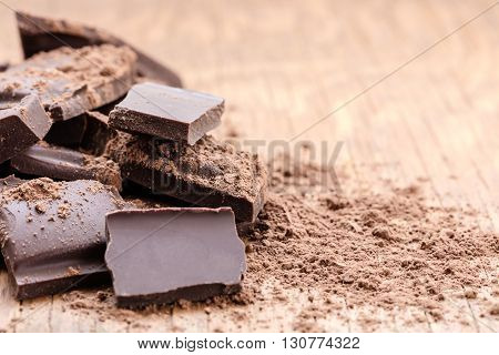 pieces of chocolate closeup on wooden background