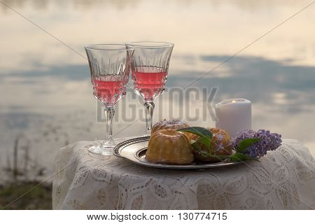 two glas of pink wine, candle and cakes