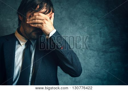 Unhappy businessman under stress after business project failure hand covering eyes.