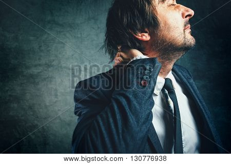 Pain in the neck of a businessman stressed businessperson in elegant suit suffering from neckache.
