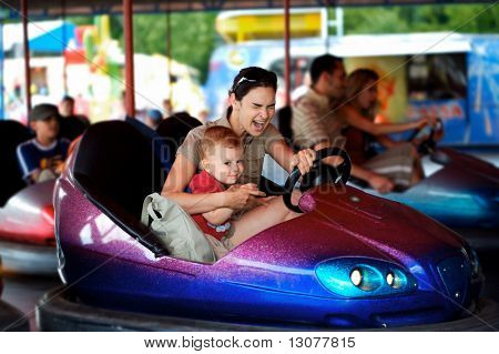 Mother and 2 years old baby pay drive dodgem together in the theme-park. poster