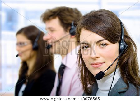 Customer service team working in headsets, smiling.