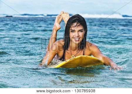 Attractive young female surfer lying down on her surfboard, paddling with arms