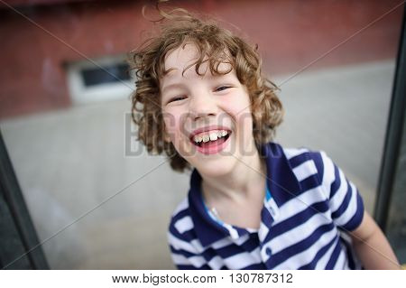 Skinny boy in a striped T-shirt laughing happily.
