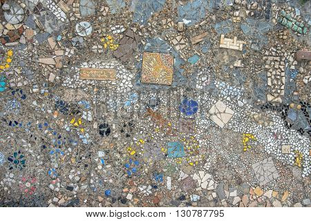 Wall made of colorful mosaic broken tiles stones and ware splinters
