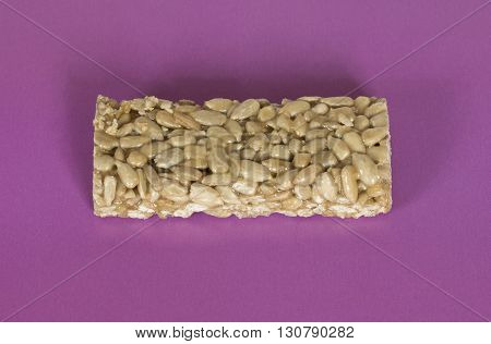 Seed brittle (sunflower brittle) on a purple background.
