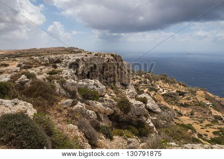 Dingli Cliffs one of the most beautiful parts of the shore at the island Malta. Water of the Mediterranean sea. Cloudy sky