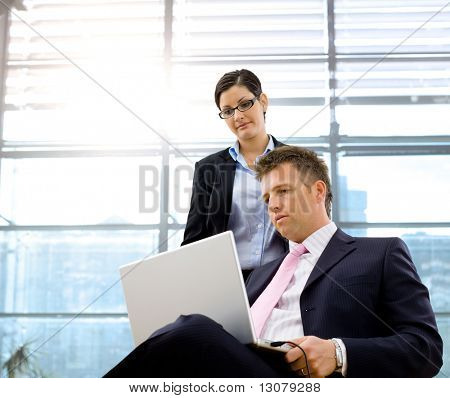 Serious mature businessman sitting and using laptop computer, businesswoman standing and working together.