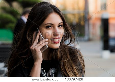 Woman phone talking. Closeup young happy beautiful smiling woman girl lady talking on mobile cell phone isolated cityscape outdoor street background. Positive face expression human emotion attitude