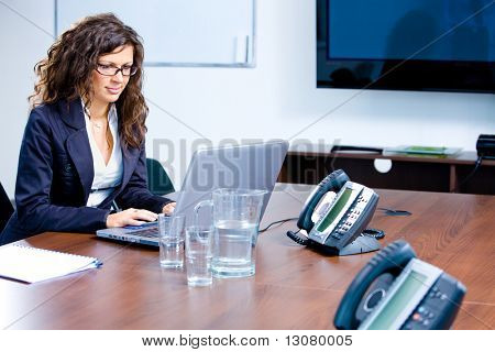 Happy young businesswoman working on laptop computer at office in meeting room, smiling.