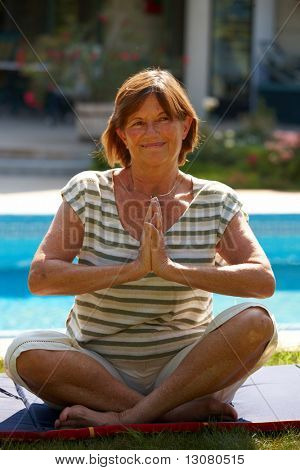 Happy active senior woman doing yoga exercise at home, smiling.