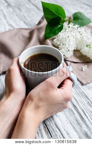 Coffee cup in female hands on a wooden table