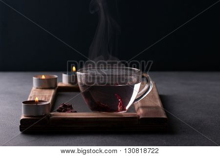 Tea ceremony. Herbal hibiscus tea in a glass cup on a slate chalk board. Tea light candles