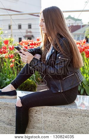 Young woman in black coat and jeans is sitting on the stone parapet holding a cellphone in the hands red flowers behind her