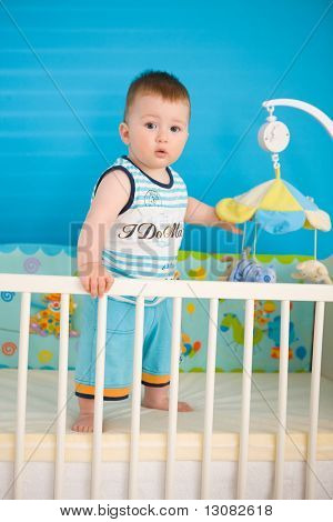 Baby boy ( 1 year old ) standing in baby bed at children's room.