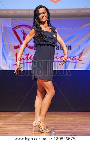 MAASTRICHT THE NETHERLANDS - OCTOBER 25 2015: Female fitness model Vanessa Leenkneght in evening dress shows her best in championship on stage at the World Grandprix Bodybuilding and Fitness