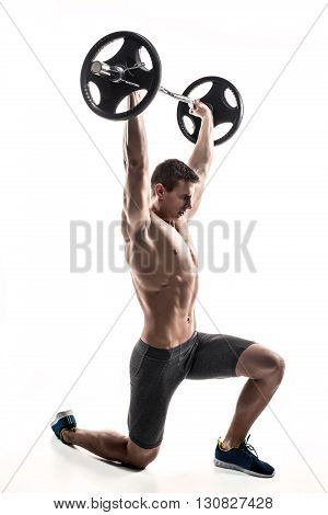 Muscular mighty man standing on knee and holding barbell over his head. Isolated on white background.