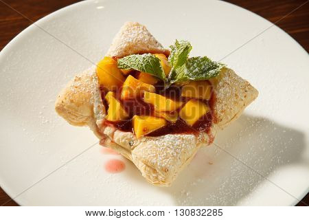 Tasty cake with fresh fruit and mint on a plate