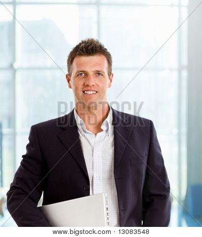 Happy businessman smiling at office lobby.