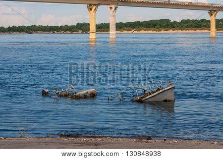 Rusty sinking vessel in a blue river