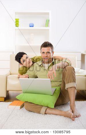 Junges Paar mit Laptop-Computer zu Hause, am Boden sitzen und liegen auf Couch, umarmen.