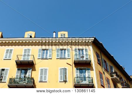 Apartment building in Nice, France, with balconies and a blue sky background.