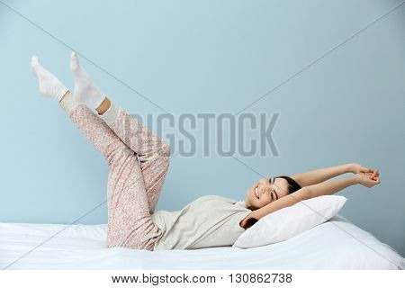Young woman in pajamas stretching herself on bed over blue background