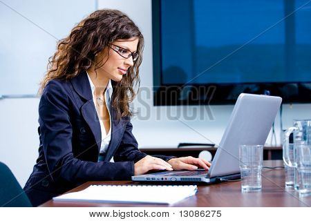 Young happy businesswoman working on laptop computer in meeting room at office, smiling.