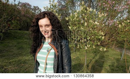 Pretty brunette long curly hair girl closeup portrait outdoors in the green park in spring. Woman looks at the sunset smiles laughs and flirts skittish. Springtime concept.