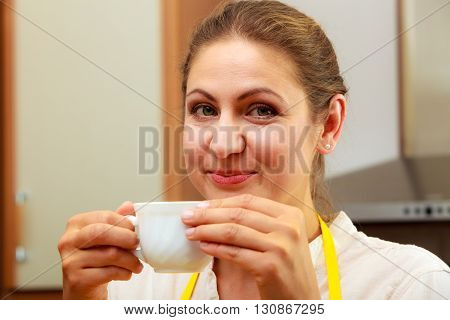 Mature woman drinking cup of coffee in kitchen. Housewife female with hot energizing beverage. Caffeine energy.
