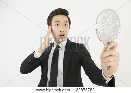 Asian young businessman in a black suit, looking at himself in a hand mirror