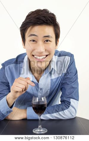 Asian young businessman pointing a glass of red wine